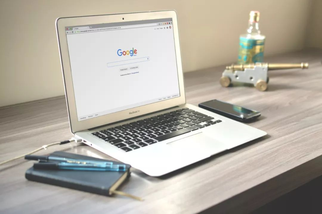 Searching google in laptop with ballpen and cellphone
